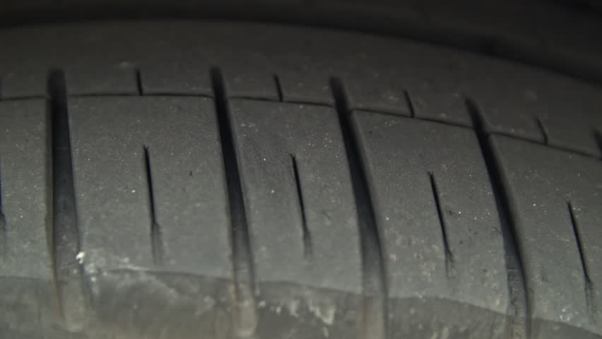 Car tyre tread close up HD stock footage. A small dolly camera move over a typical automotive tyre which is slightly worn. ProRes.