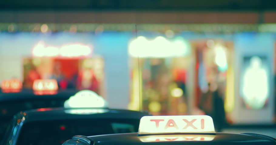 Roofs of taxi cabs with lit symbols on city street at night