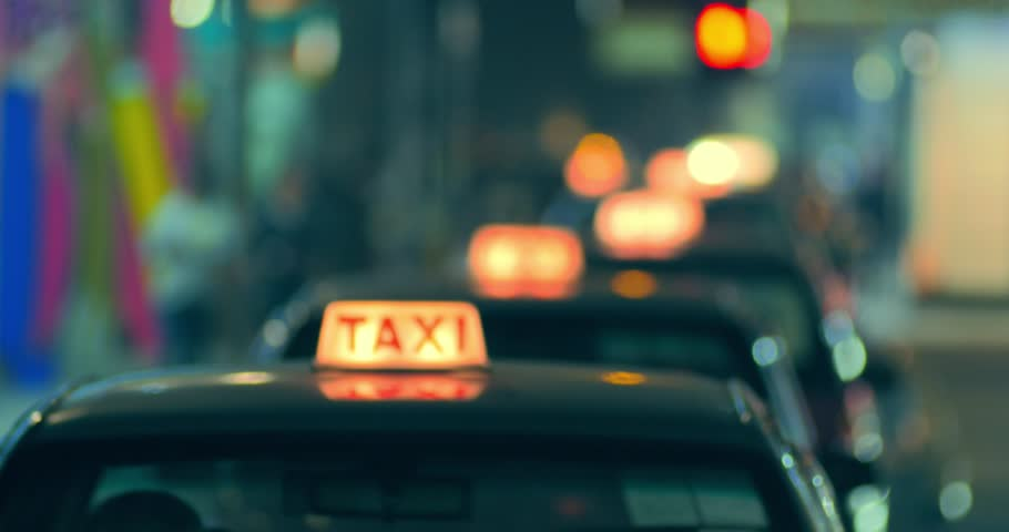 Row of taxi cabs moving on street at night in Hong Kong downtown