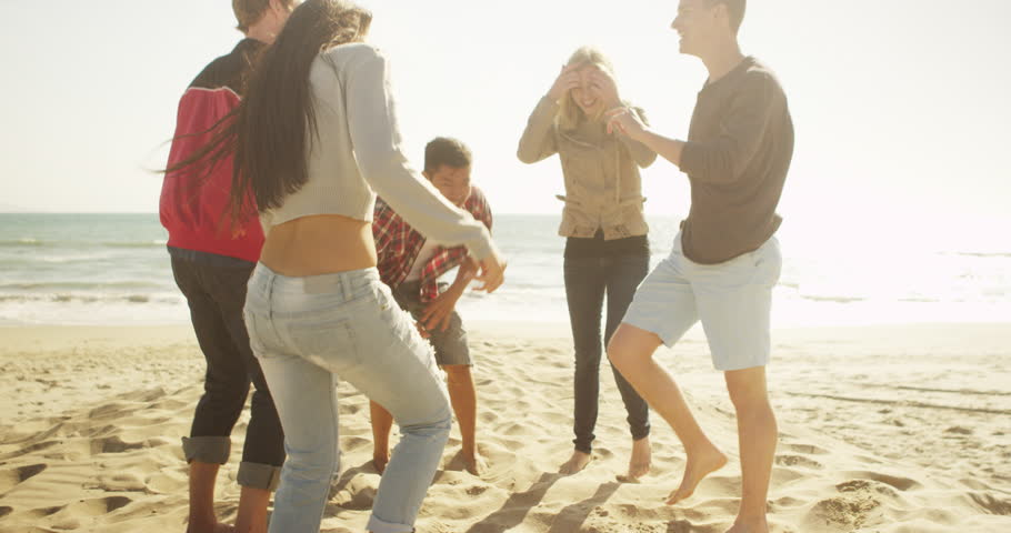 Happy young latino woman dancing on the beach with group of multi ethnic friends