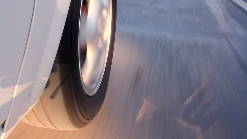 Rolling rubber tire of white car on the asphalt road. Close up of driving. Car mounted camera, on tire.