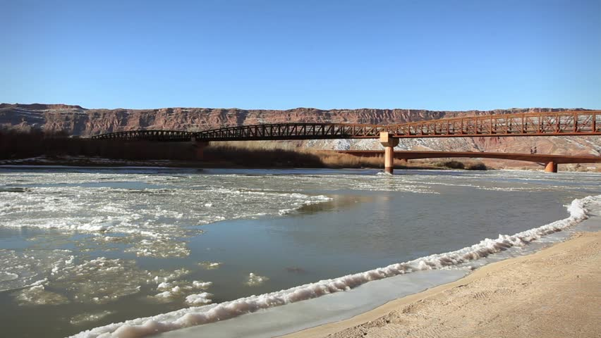 Frozen winter Colorado river and bridge Moab Utah