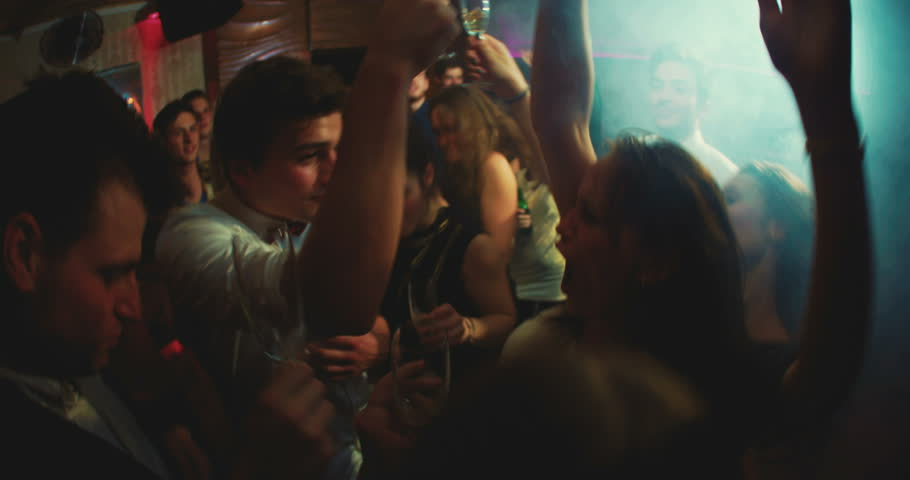 Young man dancing on a dance floor having fun with his friends with a bright light shining behind him - 4K stock video clip