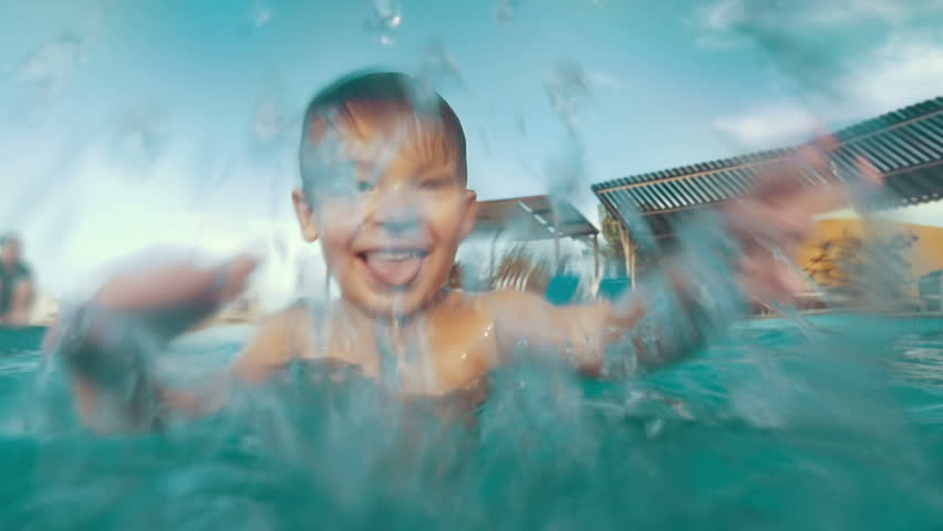 Slow motion of a child playing in the pool. Happy boy having fun on vacation. Close-up shot of water splashes - HD stock footage clip