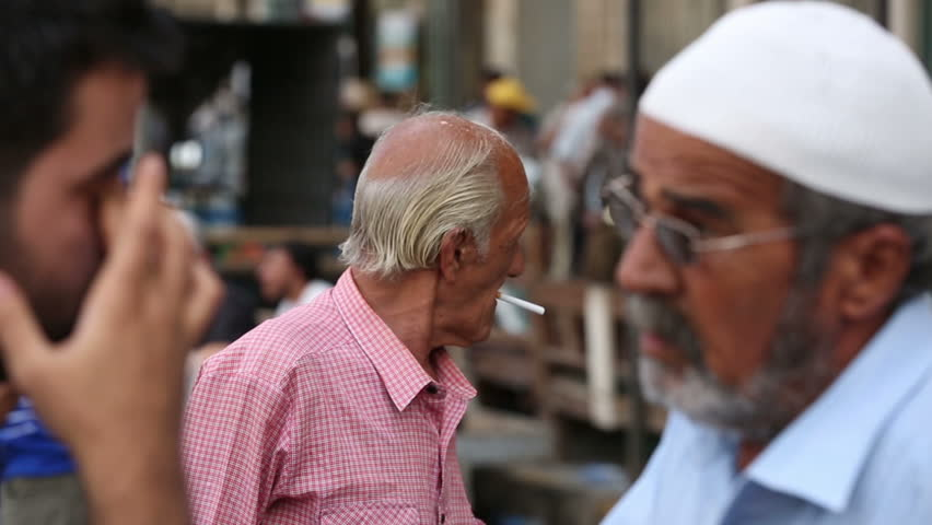 BAGHDAD, IRAQ - MAY 2015: Iraqi man lights a cigarette at Mutanabbi Street in Baghdad. Mutanabbi Street where writers and intellectuals meet is the historic center of Baghdad bookselling