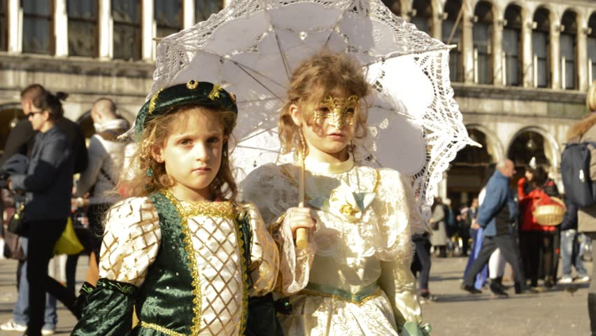 Venice, Italy - february 2015 - Carnival of Venice - two costumed girls pose for tourists in St Mark's square, during the festival, proudly displayed by their family - HD stock footage clip