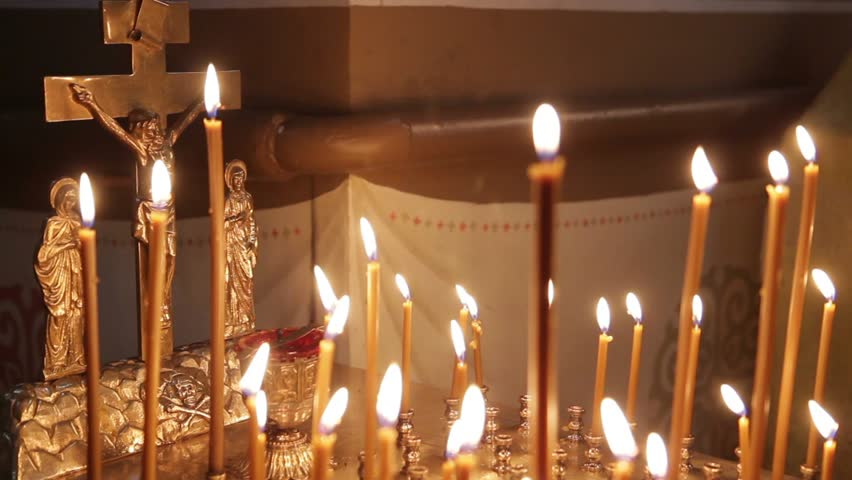 The Orthodox Church. Woman's hand puts the burning candle in front of the symbol of the crucifixion. There is a sound intershum.