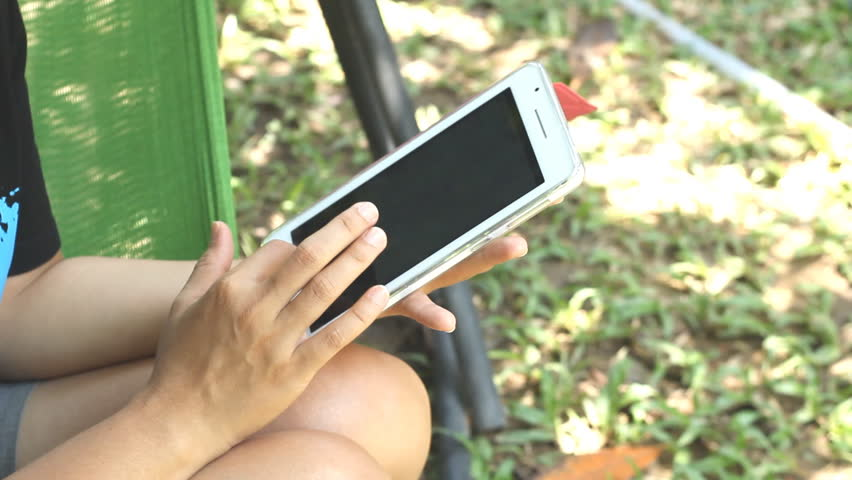 Close-up of woman play on digital tablet in garden - HD stock video clip
