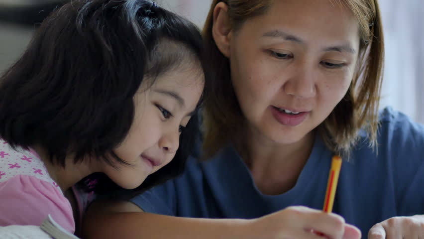 Little Asian girl with mother doing homework in the bed room - 4K stock footage clip