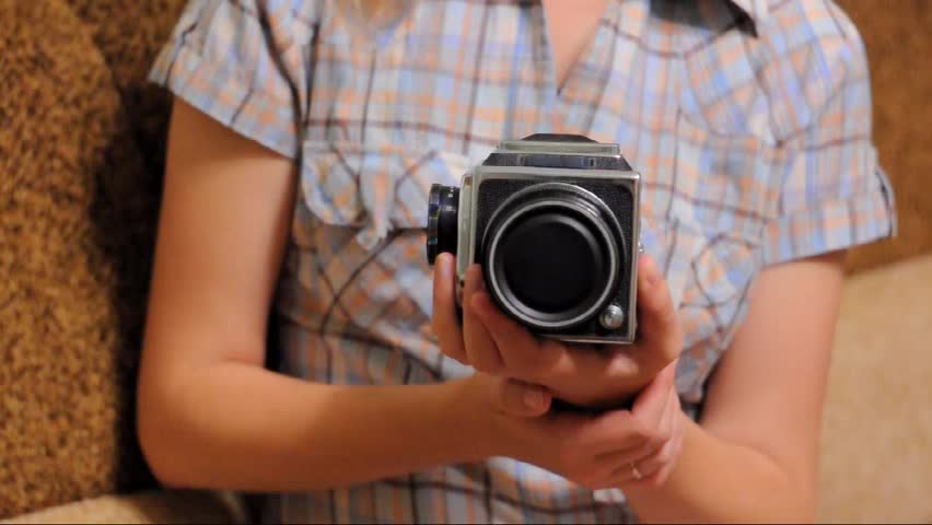 Young girl holding a model of the old medium format fotoappara . Open the camera lens, adjusts the aperture and focus, shoot. The camera shoots on 6x6 medium format film .