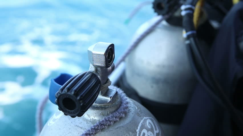 assistant unbinds silver metal oxigen cylinder for diving from boat - HD stock video clip