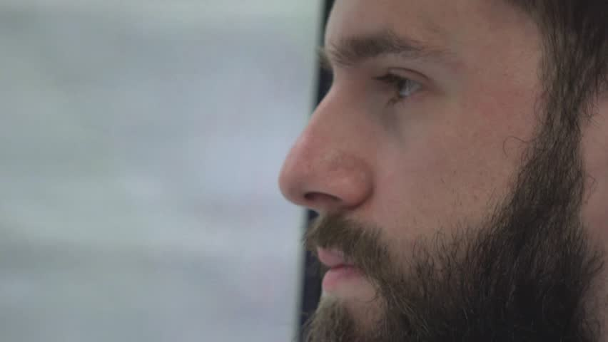 young handsome hipster man traveling by public transport and looks out of the window - closeup