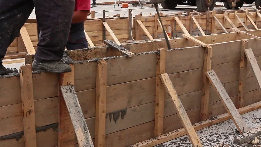 Concrete is being poured with continuous casting. Workers are pouring cement in the wooden formwork at construction site.