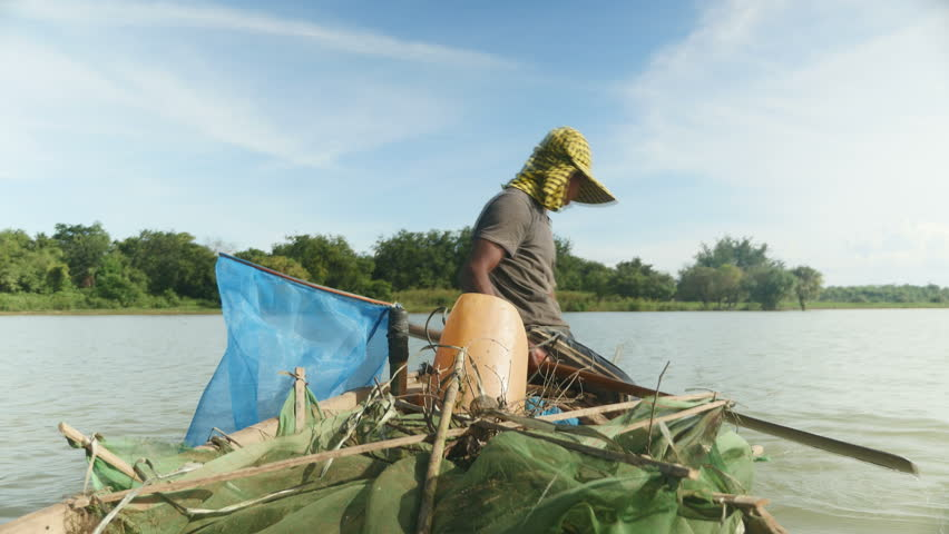 Fisherman in dugout canoe pulling drop net out of the river, catching shrimps and  throwing picked it into net hung from boat
