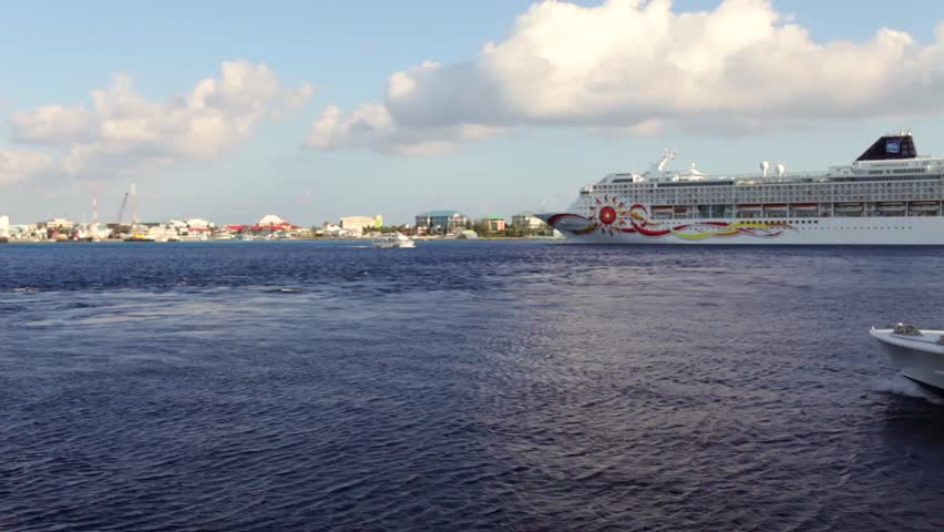 GRAND CAYMAN, CAYMAN ISLAND - 20 JULY 2012: Carib Empress tender boat sailing aside of NCL large cruise ship