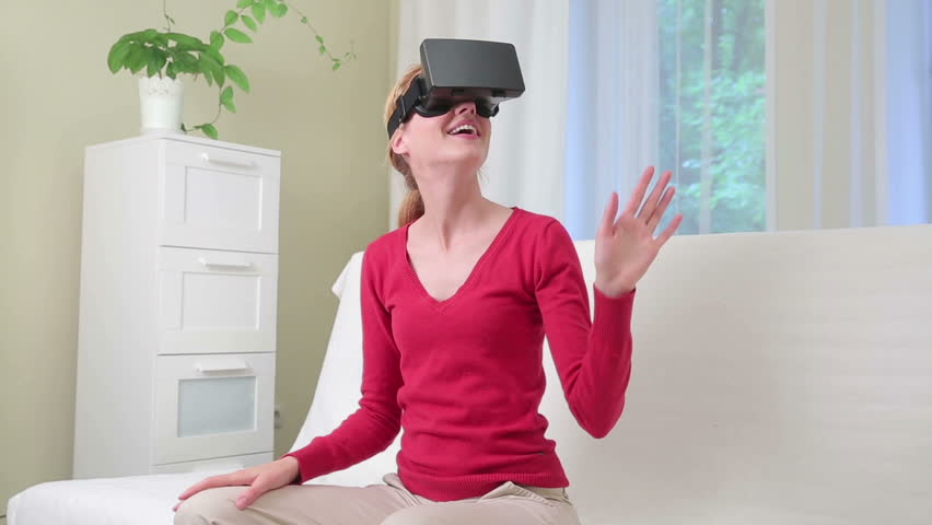 Virtual reality mask. Attractive young woman having fun uses head-mounted display in the interior.