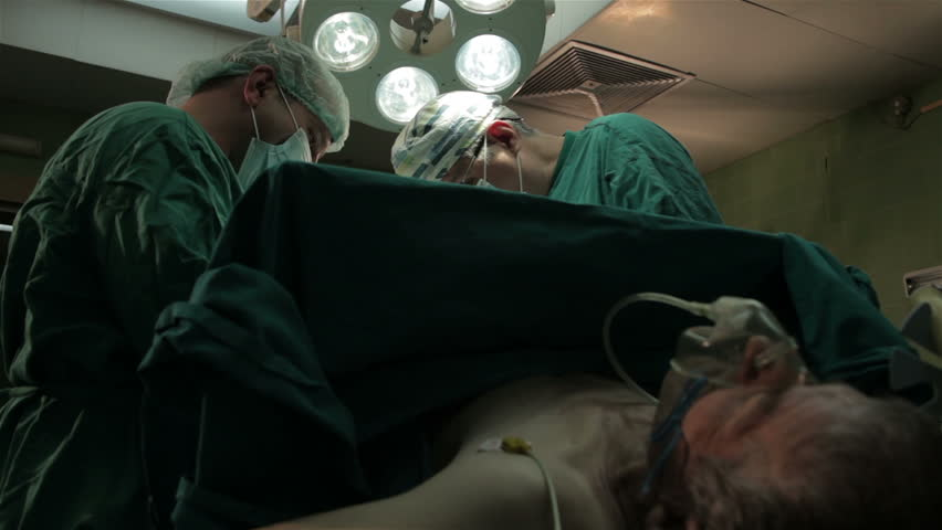 Patient under anesthesia lying on operating table and doctors perform surgical operation. Surgical team performing operation in operating room. doctor making bloody cut with scalpel. Surgery on clinic
