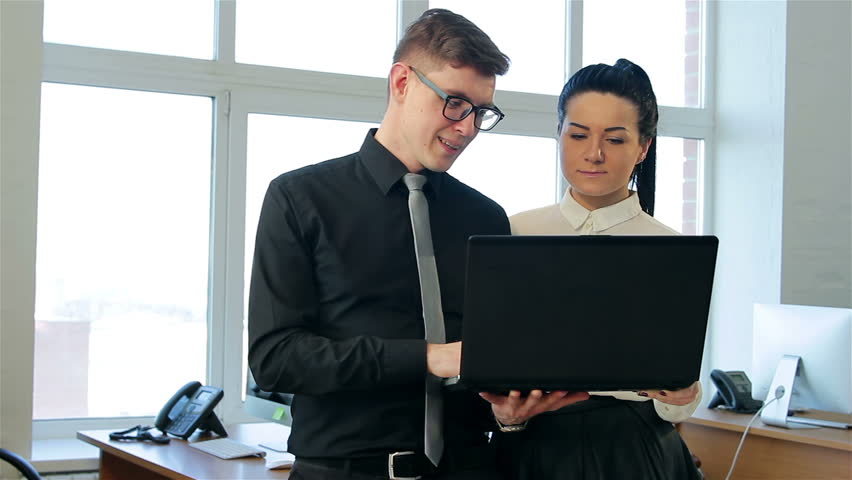 Business people talking near the laptop. Man showing on the laptop screen and talking to woman