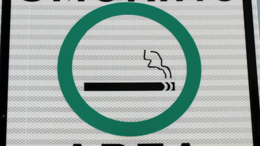 Closeup Smoking Area sign, pan out to revel a polluted smoggy sky and a smokestack gently emitting orange smoke