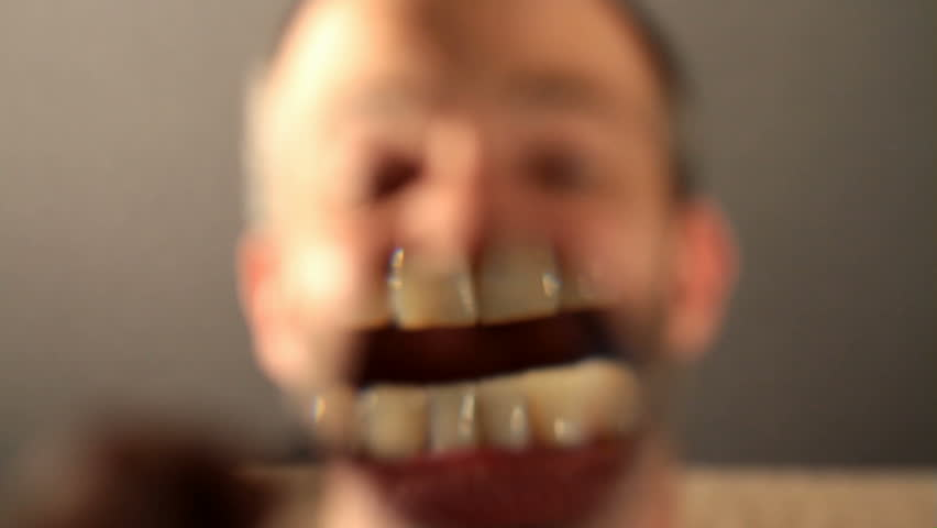 Static medium long close up shot of a mouth enlarged by a magnifying glass making clapping teeth movements with a anonymous male face in the background making chattering facial expressions.
