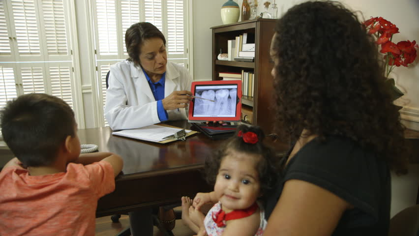 A Hispanic dentist sitting in her office with a mother and her children going over dental x-ray image displayed on a tablet pc. - HD stock video clip