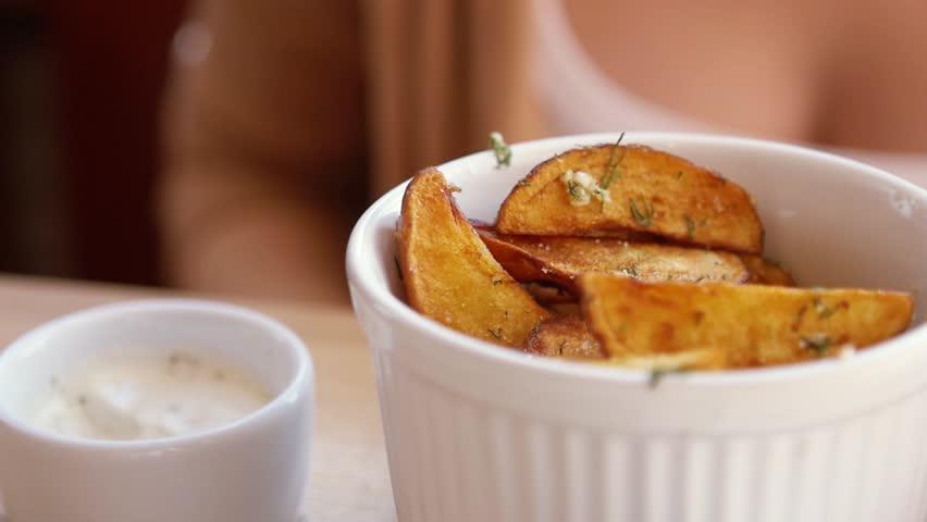 SLOW MOTION: young caucasian girl eats fresh fried potatoes - HD stock video clip