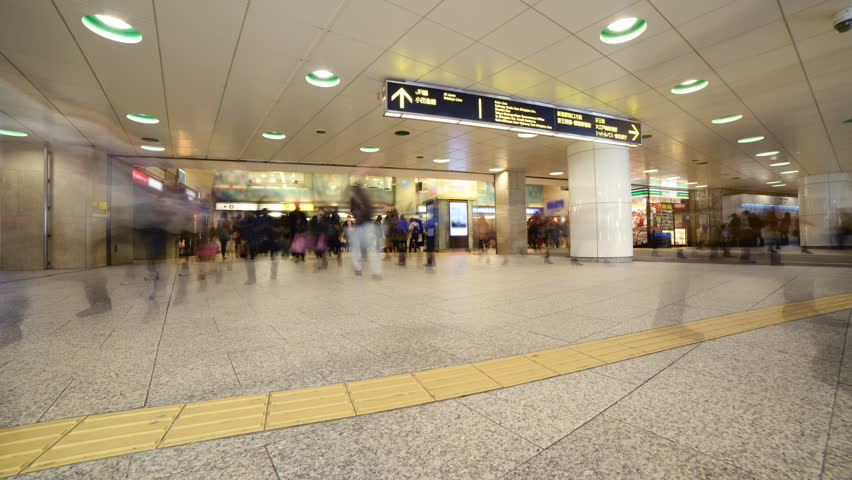 Time lapse footage with zoom in motion of anonymous rush hour commuters at Shinjuku Station in Tokyo, Japan