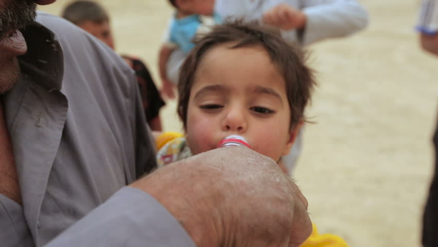 ANBAR, IRAQ - 28 MAY 2015: Thirsty Iraqi man and child displaced from Ramadi battles drink water