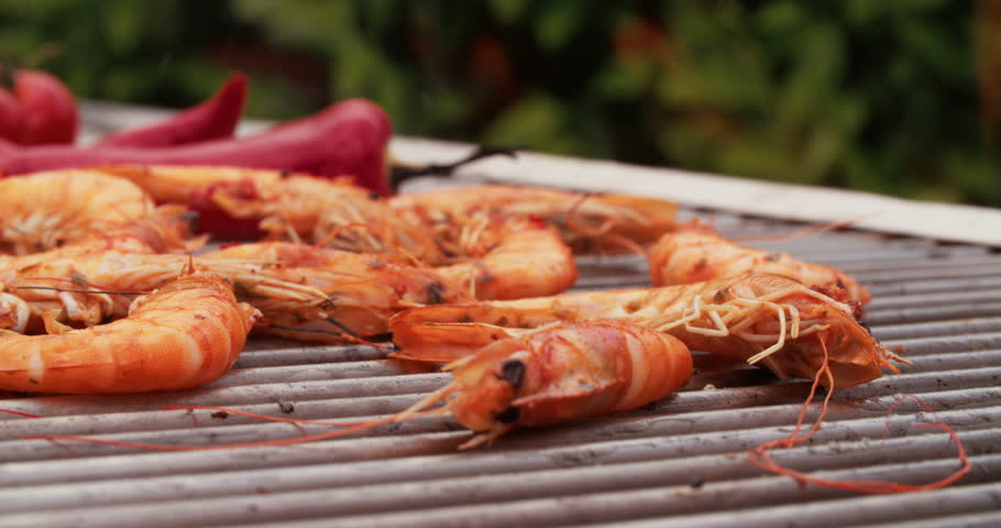 Closeup of fresh prawns with a spicy chillie seasoning cooking deliciously on a barbecue grill outdoors in Slow Motion