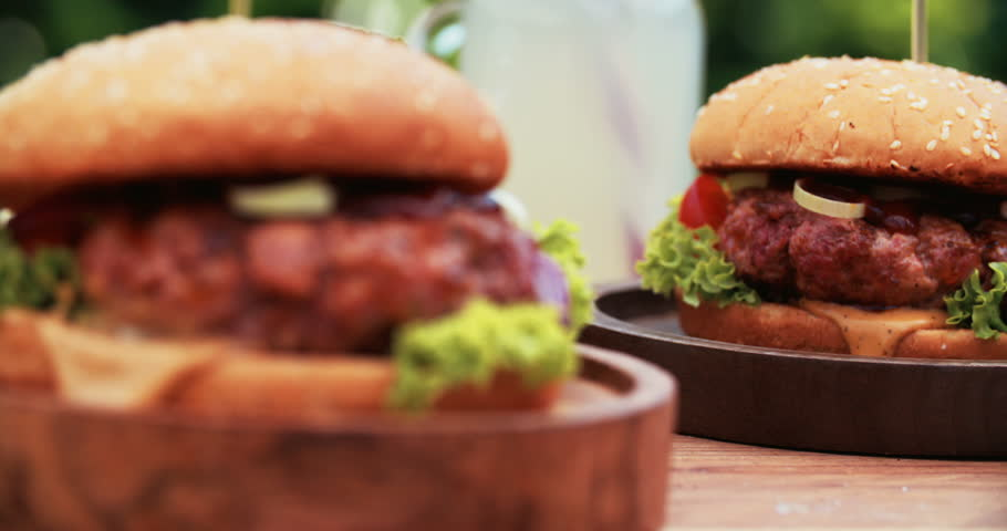 Closeup of delicious gourmet burgers with fresh tomato, onion and lettuce, cheese running over the bun and prime beef patties, placed on wooden plates - 4K stock footage clip