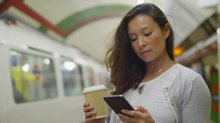 4K Attractive woman in an underground subway station checking her phone as a train arrives in slow motion, shot on RED EPIC