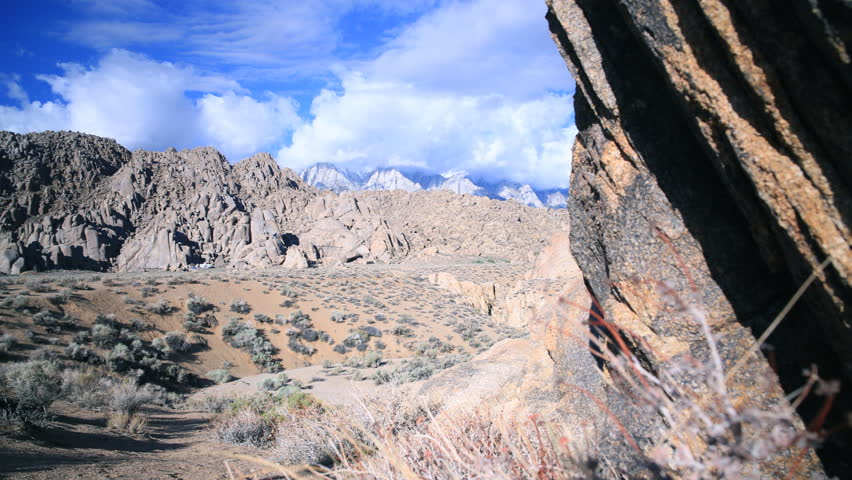 3 axis motion controlled time lapse footage with dolly up, tilt up & pan right motion of rugged rock formation and cloudscape at Alabama Hills in Sierra Nevada Mountains in California - 4K stock video clip
