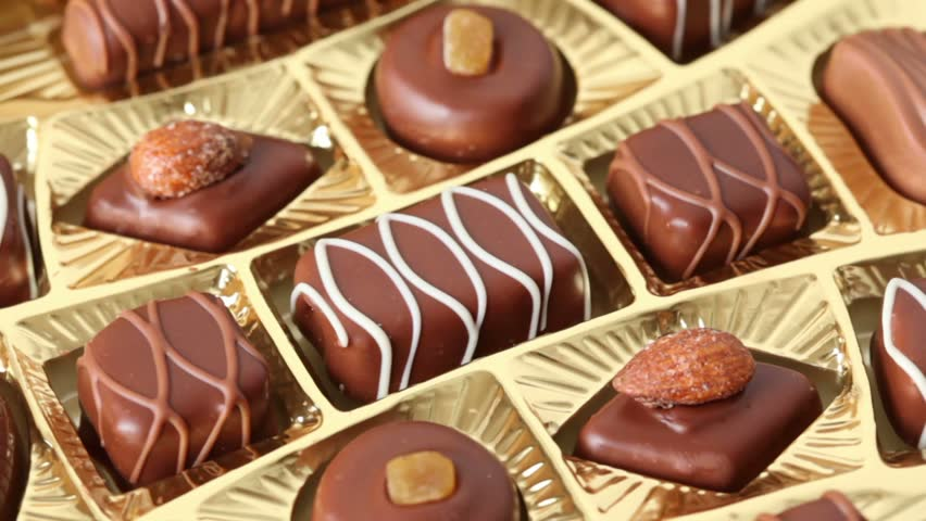 closeup of sweet chocolates in golden box rotates - HD stock footage clip