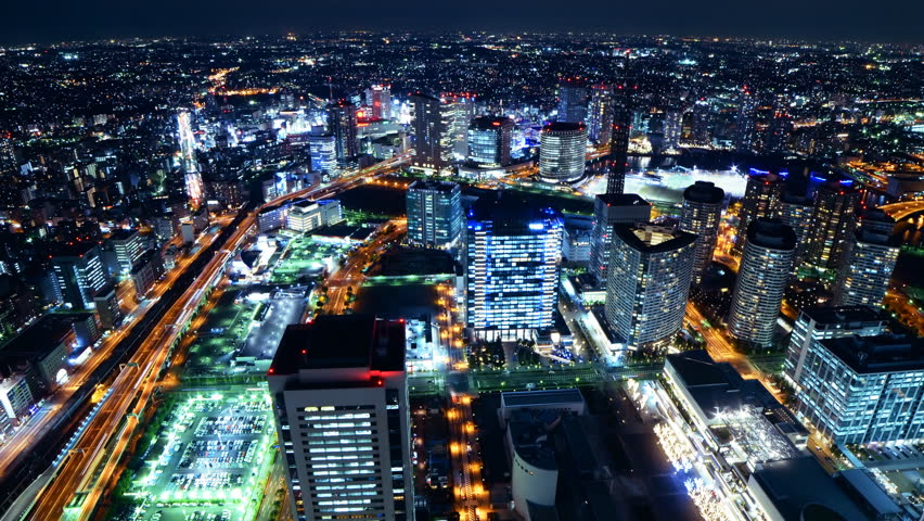 Time lapse footage with zoom out motion of metropolitan cityscape at night shot from Yokohama Landmark Tower in Japan