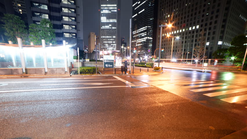Motion controlled pan right / tilt up time lapse footage with zoom in motion of skyscrapers over an intersection in the rain at night in Shinjuku, Tokyo, Japan