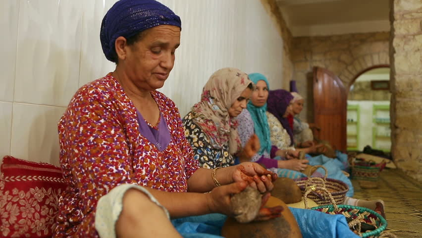 ESSAOUIRA,MOROCCO - July 25, 2015 : Berber women produce Argan oil in a traditional way in Morocco.They crack Argan hard-shelled nut which is collected from the Argan trees.