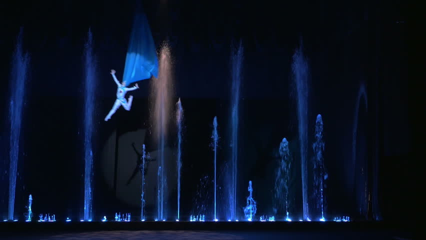 Aerial performer flying over the stage during the theatrical show. Water fountains are playing on the background.