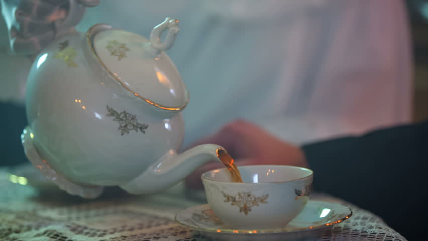 Close up RAW footage of a lady with a tea pot pouring a tea in the cup on the wooden table, historic footage.