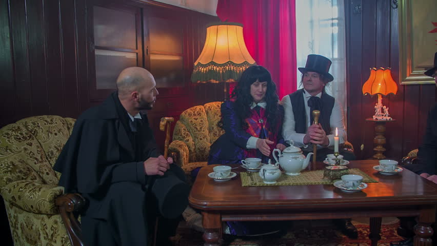 Host invites the guests to seat down in the living room for a cup of and a small talk, vintage footage in slow motion.