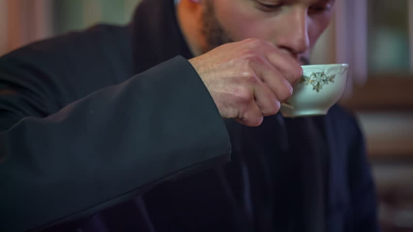 Man is seating in the vintage dining room and drinking tea from a small cup, historic close up RAW footage.