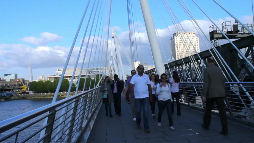 LONDON -JUNE 5: Unidentified tourists and locals on Haugerford Bridge over  the Thames in late afternoon light  on June 5, 2015 in London, UK. Time lapse - HD stock footage clip