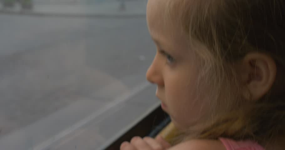 Little Blonde Girl in Pink Shirt is Sitting at the Window in the Bus, Tram, Trolleybus, Looking through the Window at the City, Lviv, Ukraine, People are Walking By, Cars, Girl Have Leaned Her Head