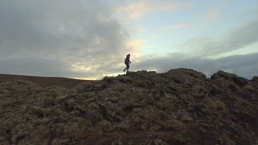 AERIAL: Young woman hiking up on the edge of volcanic crater in autumn evening