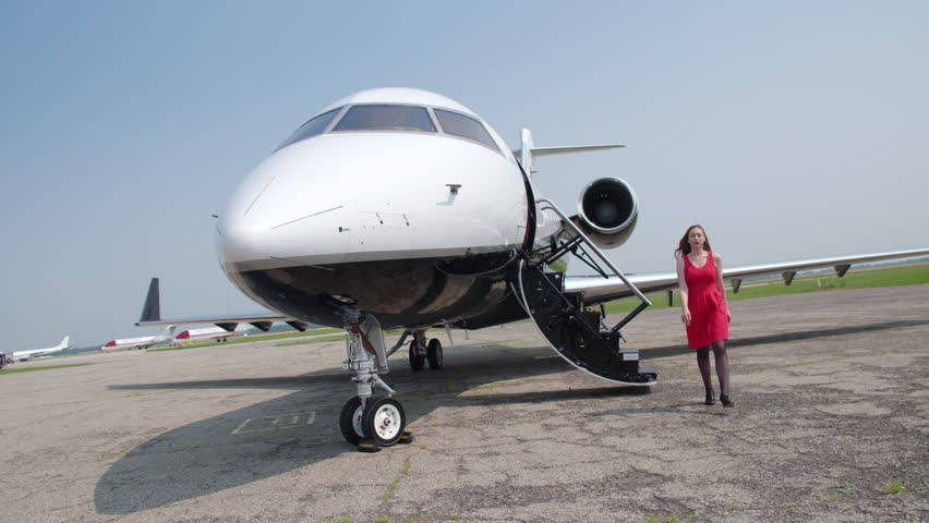 Attractive brunette in a red dress walks down steps and away from an executive jet.  Wide view with partial speed ramp, originally recorded in slow motion 4K at 60fps.