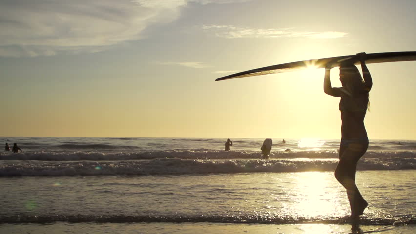 Silhouette Surfer Girl Walking On Beach at Sunset In Slow Motion  - HD stock footage clip