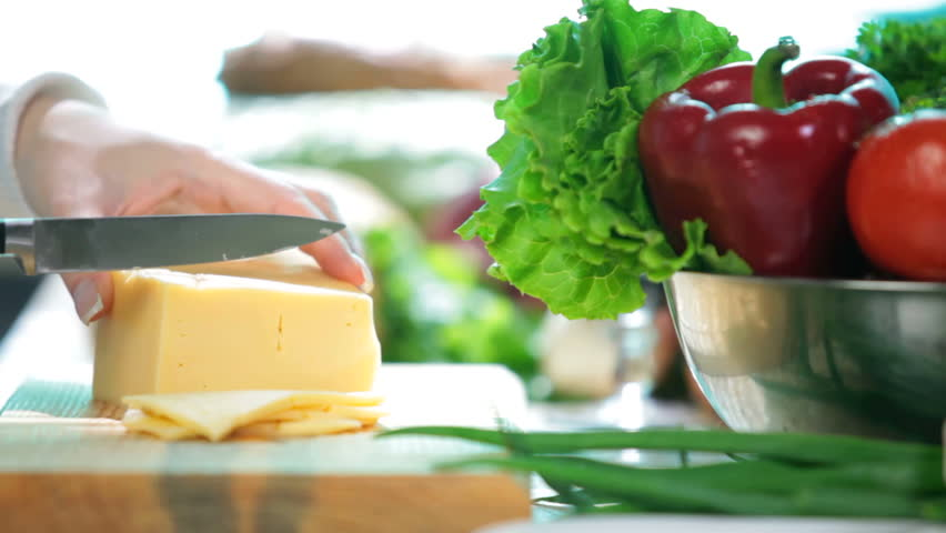 women hands slicing the cheese on the kitchen table