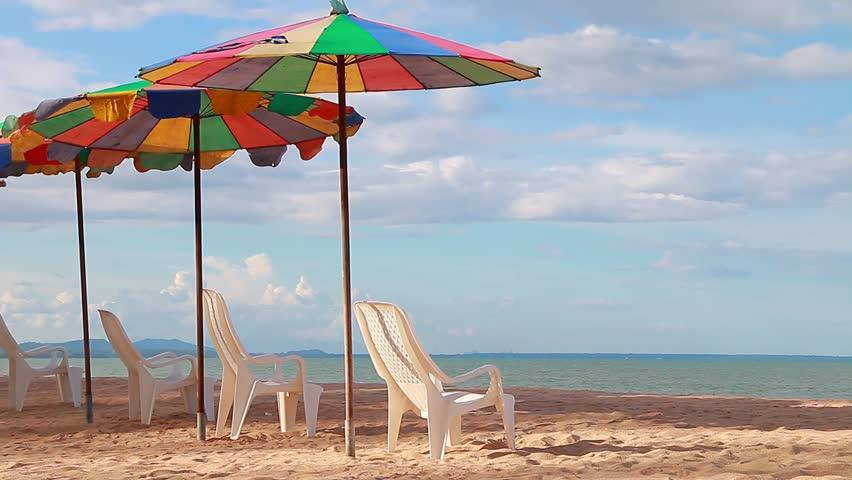 Beach chair and umbrella on sand beach - HD stock video clip