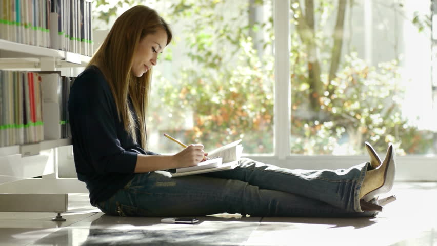 female college student sitting on floor in library, reading book and taking notes.  - HD stock footage clip