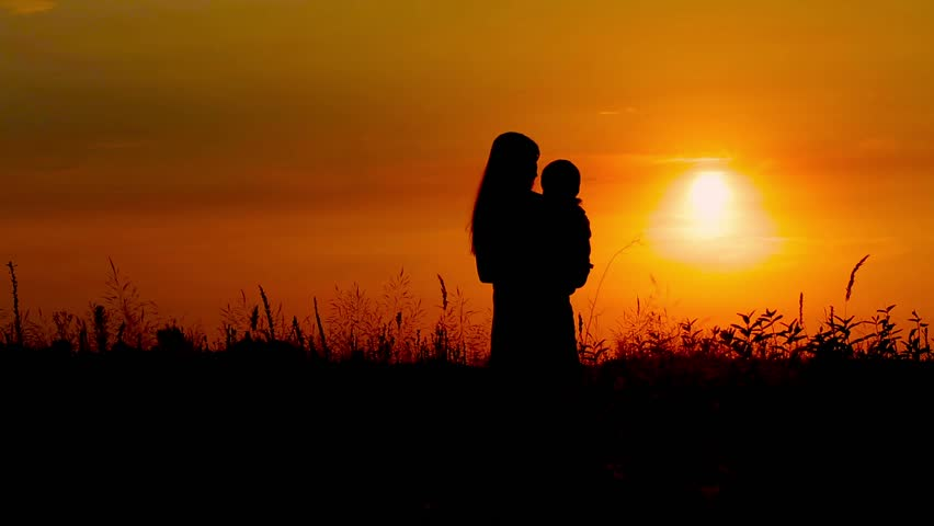 Mother and baby at sunset. Motherhood at sunset. We see their silhouettes. | Shutterstock HD Video #11293652