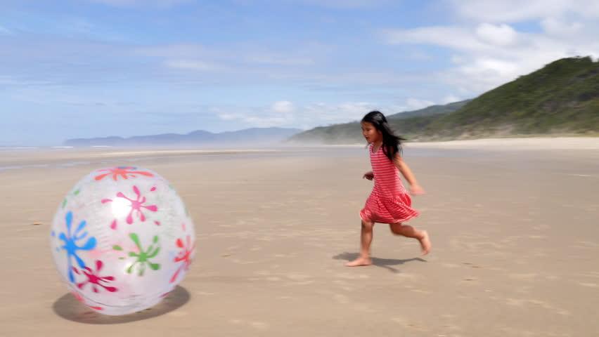 Girl running and kicking large ball at beach